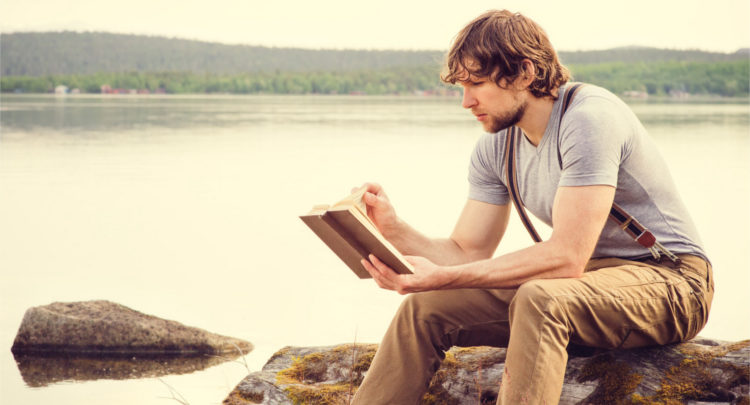 guy reading an outdoor book sitting by a lake on a stump
